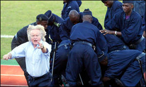 Cameroon's coach Winfried Schafer appeals for help as his colleague is set upon by police
