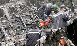 South Korean rescue workers examine the wrecked fuselage of an Air China plane, 16 April 2002
