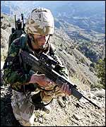 A marine from 45 Commando crouches with his weapon in Ginger Valley