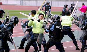 Riot police attempt to control a mob of hooligans during a security exercise at Yokohama Stadium