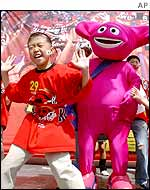 A South Korean football fan dances along with mascot doll Kaz, Seoul