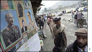 Afghans look at Zahir Shah's psoters