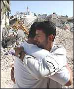 Two Palestinians embrace after troops leave Jenin