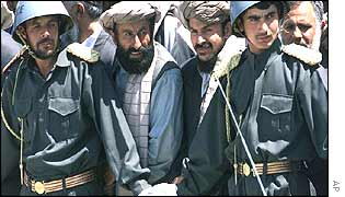 Afghan police officers hold back crowds