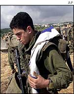 An Israeli soldier carries his nation's flat