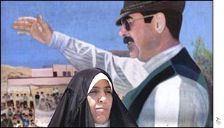 Woman passes poster of Iraqi leader Saddam Hussein