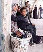 Palestinian woman and her family wait for a chance to cross the street