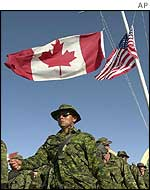 Canadian troops march past US and Canadian flags at half-mast at Kandahar airport