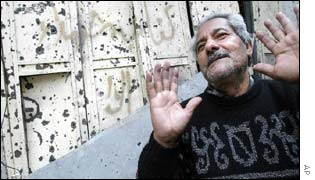 A Palestinian man gestures outside his bullet-ridden shop