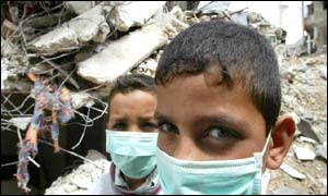Palestinian children shield their faces from the smell of rotting food and decomposing bodies