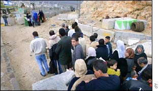 Palestinians line up at a checkpoint on their way home
