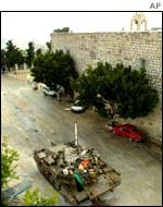 An Israeli tank patrols the area surrounding the church