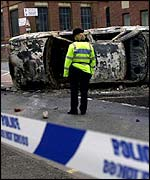 Police cordon at a burnt out car