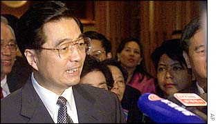 Hu Jintao (left) speaks to reporters upon his arriving at a hotel in Kuala Lumpur, 23 April 2002.