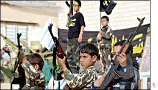 Palestinian boys carry guns at a funeral