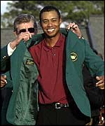 Tiger Woods slips on the famous green jacket at Augusta in April