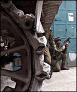 Israeli soldiers crouch near a tank in Bethlehem
