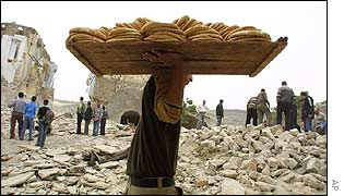 Man carries bread through Jenin camp ruins