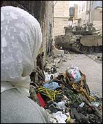 Palestinian woman watches Israeli tank in Bethlehem