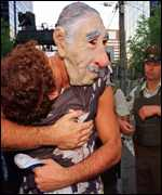 [ image: A man wearing a Pinochet mask is embraced by a fellow supporter]