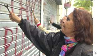 Angry Argentines hammer the shutters at a bank