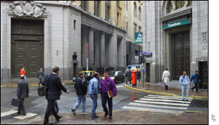 Pedestrians walk past a closed bank in the financial district in Buenos Aires