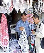 A man selling keffiyehs in an Amman market