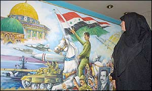 An Iraqi woman looks at a mural of Saddam Hussein 'liberating' Jerusalem