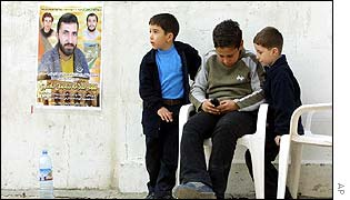 Palestinian children play near a poster of a dead fighter