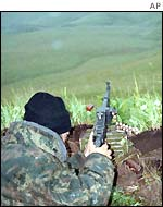 An Islamic militant aims his machine gun at a position in Botlikh region of Dagestan