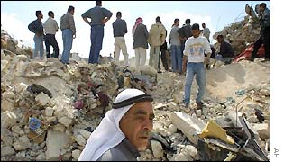 Palestinians watch digging through rubble of destroyed houses in Jenin refugee camp