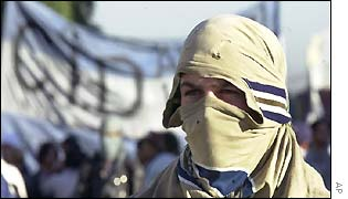 A masked demonstrator marches to Buenos Aires Plaza de Mayo during a protest of several hundred unemployed people