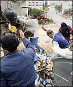 Refuse workers clear rubbish off the streets