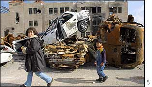 Children walk past burnt out cars in the cenre of Ramallah