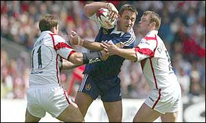 Wigan prop Craig Smith is tackled by Chris Joynt and Kieron Cunningham