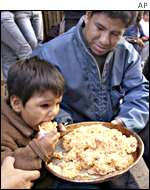 A boy eats food from a soup kitchen on a protest march by the unemployed
