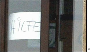 A sign calling in German for help is seen at the school window