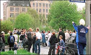 Staff, students and pupils wait outside the school