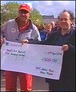 Ian Botham accepts a cheque from Andy Roberts of BBC Wales News New Media