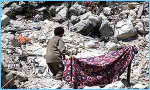 A Palestinian boy tries to pitch a tent on the rubble of his house in the Jenin refugee camp