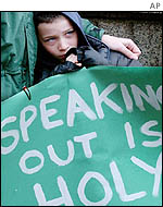 Boy holds sign urging victims to speak out