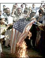 Angry Pakistanis burn a US flag in protest against its military operations