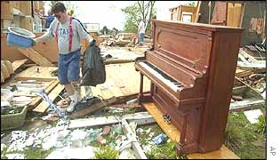 Gene Cavender carries items from a relative's home after a tornado hit Murfreesboro, Tennessee