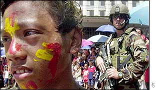A US soldier looks at a boy with face painted as he keeps guard over celebrations in Isabela city