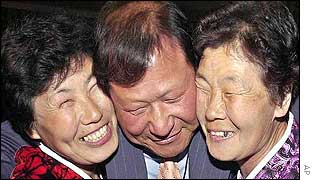 South Korean Yun Kum-chul (C) smiles with his unidentified North Korean sisters