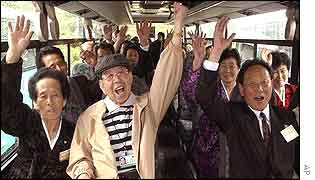 North and South Koreans cheer in a bus as they tour together to Diamond Mountain resort in North Korea