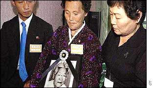 North Korean Lee Shin-Ho (C) holds the portrait of their mother