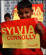 Young boy holding Sylvia Connolly poster