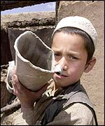 A boy in Gardez help his father clean out his bombed shop