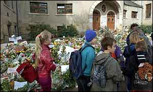 Pupils walk by a sea of floral tributes outside the Gutenberg school